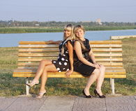 Two beautiful girls on a bench Royalty Free Stock Photos