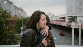 Two beautiful girls best friends met at the city bridge, hugging, kissing, talking, smiling, laughing. slow mo stock video