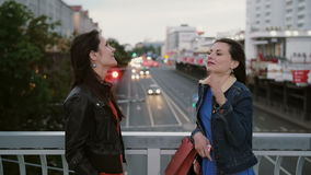 Two beautiful girls best friends standing on the city bridge, talking, smiling, laughing. slow mo. stedicam shot. Happy beautiful girls best friends standing on stock video