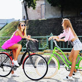 Two beautiful girls on a bicycles - outdoor Stock Photo