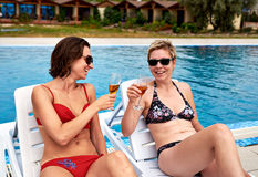 Two beautiful girls in bikini drinking champagne Royalty Free Stock Photos