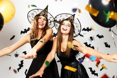 Two beautiful girls in black dresses and witch hats have fun with balloons and confetti on the background of the wall stock photos