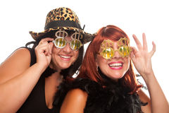 Two Beautiful Girls with Bling Dollar Glasses. Beautiful Smiling Girls with Bling-Bling Dollar Glasses and Funky Hat Isolated on a White Background royalty free stock photos