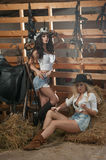 Two beautiful girls, blonde and brunette, with country look, indoors shot in stable, rustic style. Attractive women with hats Royalty Free Stock Photo