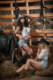 Two beautiful girls, blonde and brunette, with country look, indoors shot in stable, rustic style. Attractive women with hats royalty free stock photos