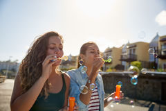 Two beautiful girls blowing some bubbles. Two beautiful young girls wearing casual clothing outside in the sunshine blowing soapie bubbles with a bright clean Stock Images