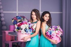 Two beautiful girls in blue dresses in studio with decor of flowers in baskets. Stock Images