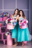 Two beautiful girls in blue dresses in studio with decor of flowers in baskets. Royalty Free Stock Photo