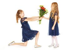 Two beautiful girls with a bouquet of flowers. Two charming little girls in a blue dresses with a bouquet of flowers Stock Photo