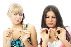Two beautiful girls  break cigarettes. Two beautiful young women  break cigarettes and frown Royalty Free Stock Images
