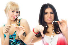 Two beautiful girls breaking cigaretts Stock Photography
