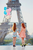 Two girls with bunch of balloons in front of the Eiffel tower Stock Photos