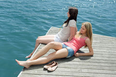Two beautiful girls in casual clothes sunbathing Royalty Free Stock Photography
