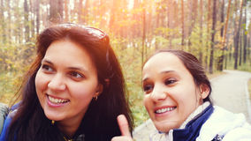 Two beautiful girls with cell phone camera taking photos selfie in autumn fall park Royalty Free Stock Image