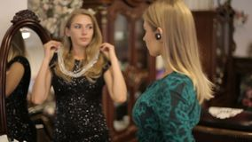 Two beautiful girls choose jewelry in front of a mirror in a chic room. Two beautiful girls in evening dresses choose jewelry in front of a mirror in a chic room stock video