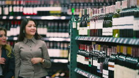 Two beautiful girls choosing the wine in the shop. The background is blurred. The camera focuses on the stage with various bottles of wine. Two beautiful friends stock footage