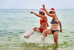 Two beautiful girls in Christmas Santa hat at the beach Stock Photography