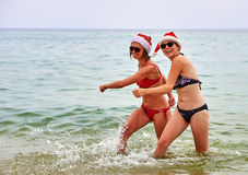 Two beautiful girls in Christmas Santa hat at the beach Royalty Free Stock Image