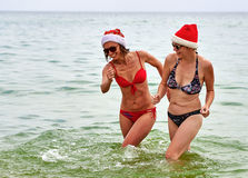 Two beautiful girls in Christmas Santa hat at the beach Royalty Free Stock Photo