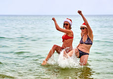 Two beautiful girls in Christmas Santa hat at the beach Royalty Free Stock Photos