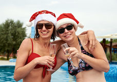Two beautiful girls in Christmas Santa hat drinking champagne Royalty Free Stock Photography