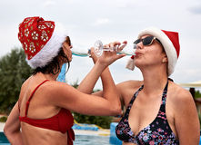 Two beautiful girls in Christmas Santa hat drinking champagne Stock Image