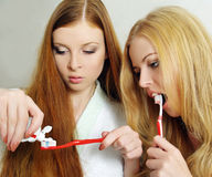Two beautiful girls clean a teeth Stock Image