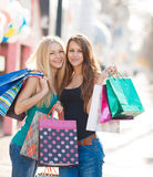 Two beautiful girls with colorful shopping bags. Two beautiful young women in T-shirts and jeans with multi-colored shopping bags in their hands on a sunny Royalty Free Stock Image