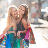 Two beautiful girls with colorful shopping bags Royalty Free Stock Photos