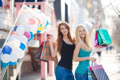 Two beautiful girls with colorful shopping bags Stock Photography