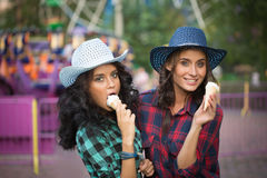 Two beautiful girls in cowboy hats eating ice Stock Image
