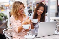 Two beautiful girls cups and laptop Stock Photos