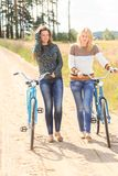 Two beautiful girls during cycling Stock Images