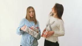 Two beautiful girls dances with festive presents at white background. Cute blonde and brunette dancing with festive gifts at a white background. Pretty ladies stock video