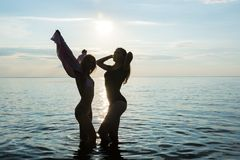 Two beautiful girls are dancing on the beach at sunset sea background, silhouettes royalty free stock photography