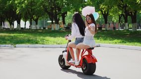 Two beautiful girls in denim shorts ride in the Park on an electric scooter in the summer