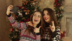 Two beautiful girls do selfie near a Christmas tree stock footage