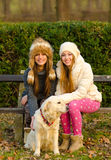 Two beautiful girls and a dog in the park Stock Photography