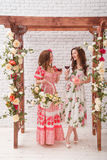 Two beautiful girls dressed in summer dresses posing near a flower arch with glasses of red wine in hands Stock Images