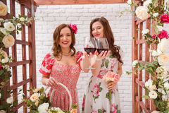 Two beautiful girls dressed in summer dresses posing near a flower arch with glasses of red wine in hands Royalty Free Stock Photo