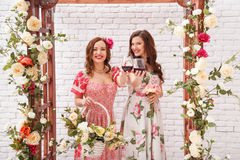 Two beautiful girls dressed in summer dresses posing near a flower arch with glasses of red wine in hands. Royalty Free Stock Photos