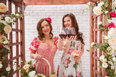 Two beautiful girls dressed in summer dresses posing under a flower arch with glasses of red wine in hands stock photo