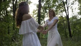 Two beautiful girls dressed in white angelic dresses dance in the green forest -. Two beautiful girls dressed in white angelic dresses dance in the green forest stock video footage