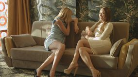Two beautiful girls in dresses and heels sit on the couch in a stylish interior and communicate. Two beautiful young girls in dresses and heels sit on the couch stock video