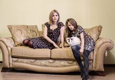 Two beautiful girls in dresses sitting on a sofa. Stock Photography
