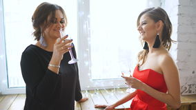 Two beautiful girls drink champagne and cheers. Women having fun laugh in bedroom stock video footage