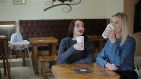 Two beautiful girls drink coffee stock footage