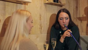 Two beautiful girls drinking champagne and Smoking hookah in a cafe. stock footage