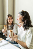 Two beautiful girls drinking coffee and smiling Royalty Free Stock Photos