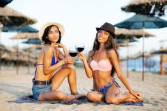 Sexy girls having a wine on a beach. Two beautiful girls drinking wine on a beach Royalty Free Stock Images